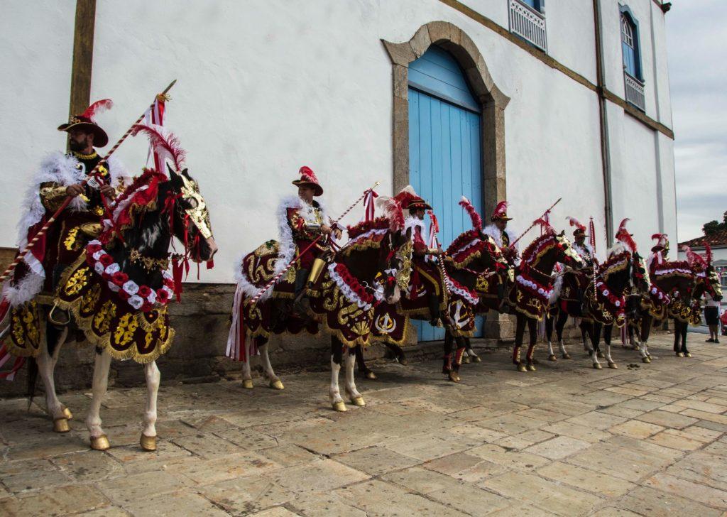 Foto de cavaleiros com roupas medievais nas cavalhadas de Pirenópolis