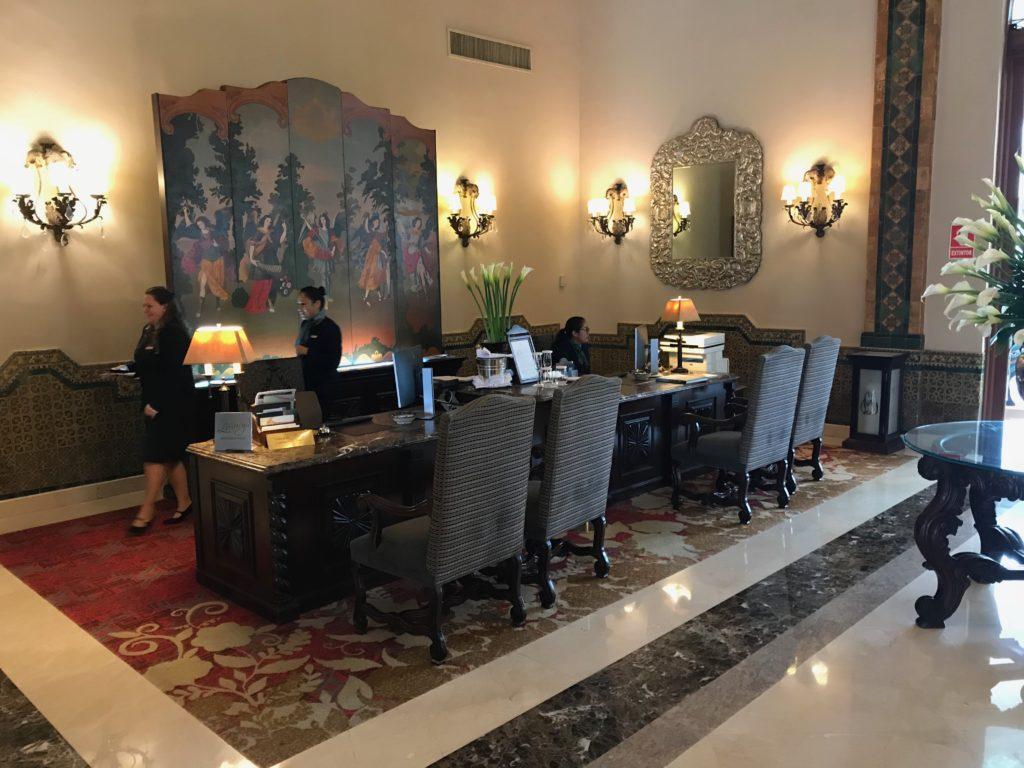 Foto do balcão de check-in do hotel, em móvel clássico de madeira escura, com cadeiras estofadas para os hóspedes.