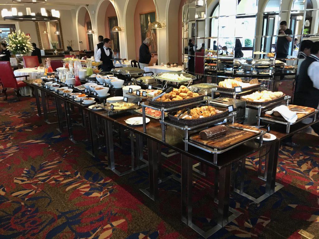 Foto da mesa do buffet de café da manhã no Country Club Lima Hotel, com pães, salgados, sucos, café, iogurte, cereais, frutas e demais opções.