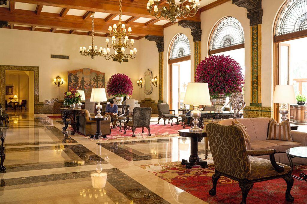 Foto do interior do saguão principal do Country Club Lima Hotel, com poltronas, tapetes, lustres, portas amplas e peças de arte.