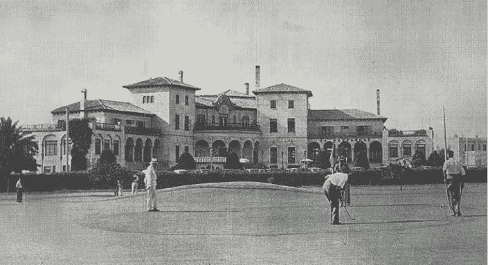 O prédio do Country Club em foto antiga, preto e branca, com hóspedes jogando golfe em frente.