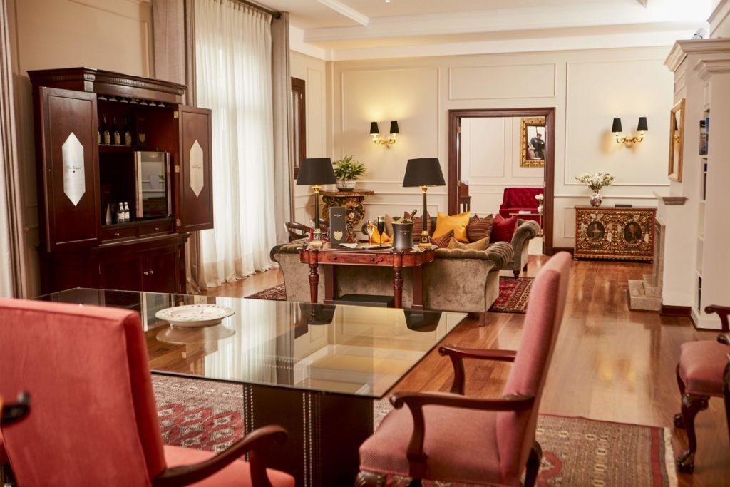 Vista de interior da suíte Dom Perignon, com mesa de jantar, adega com rótulos da marca, sofás, cortinas e obras de arte.