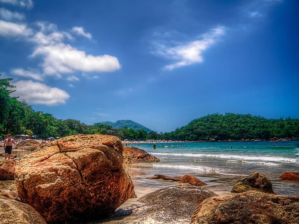 Uma das melhores praias em Ubatuba para famílias com crianças, a praia Domingas Dias pode ser vista na foto, com vegetação, mar e pedras. Foto de Rafael Vianna via Flickr