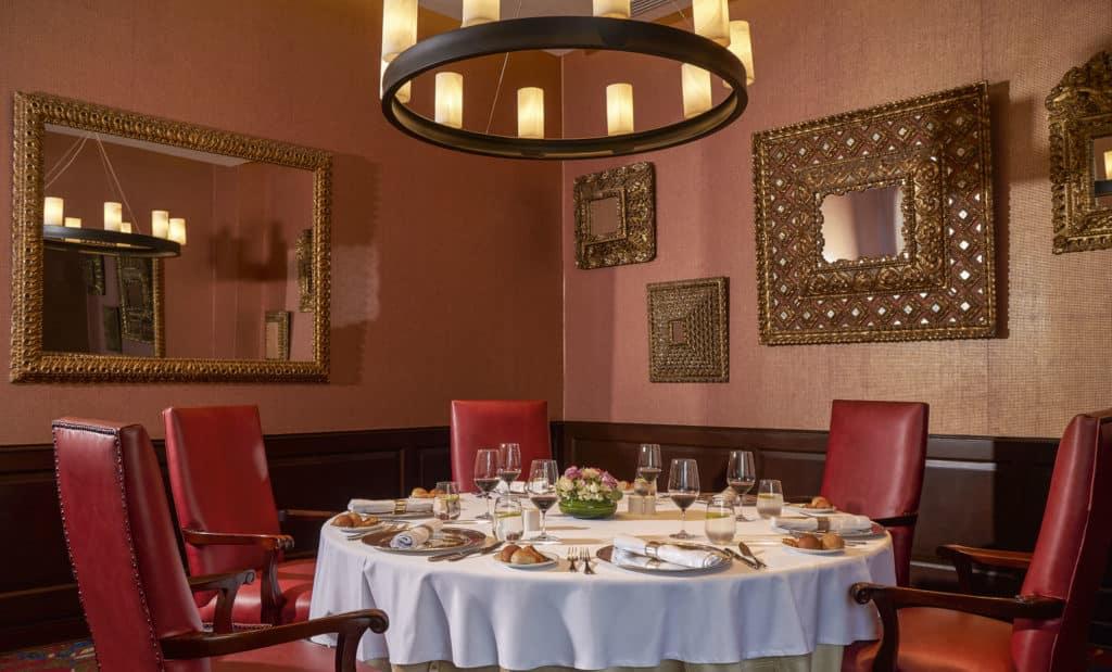 Foto com mesa redonda para jantar, cadeiras estofadas, e papel de parede rosé com espelhos em molduras douradas.