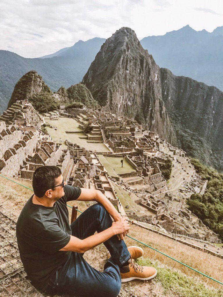 Flávio sentado em foto com vista para a cidade perdida dos incas lá embaixo, em passeio agendado com o próprio Sumaq Machu Picchu.