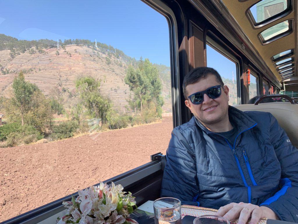 Flávio Antunes em trem de primeira classe da Inca Rail, ao lado de grande janela para apreciar a vista.