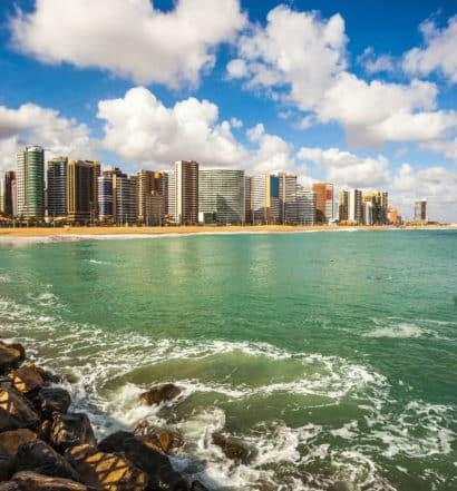 Vista da costa de fortaleza, com orla de praia repleta de prédios ao fundo e água do mar verde.