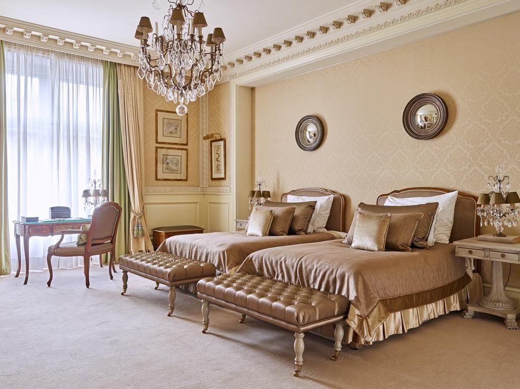 Quarto com camas e lustre suntuoso no Grand Hotel Wien