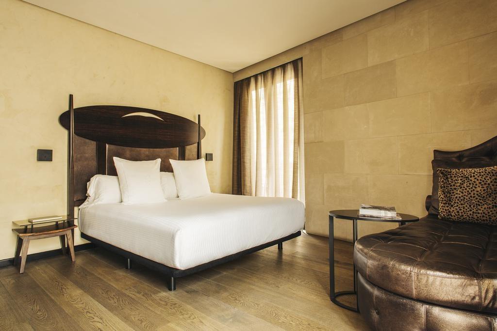 Quarto do Hotel Bagué - decoração em tons marrons e cama lençol branco