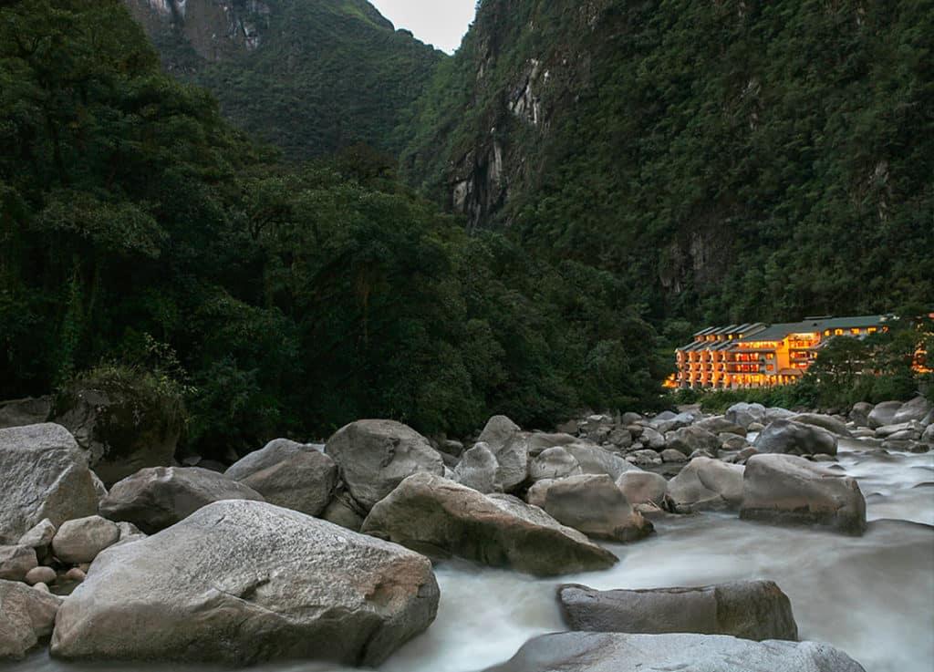 Pedras no rio Urubamba e a estrutura do hotel ao fundo, com as luzes acesas, aos pés das montanhas que cercam Machu Picchu.
