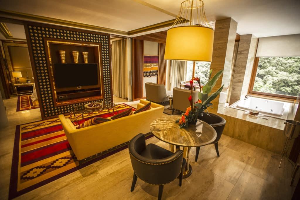 Sala de estar ampla com TV, sofá, mesa e poltronas, além de banheira de hidromassagem exclusiva com vista para o rio.