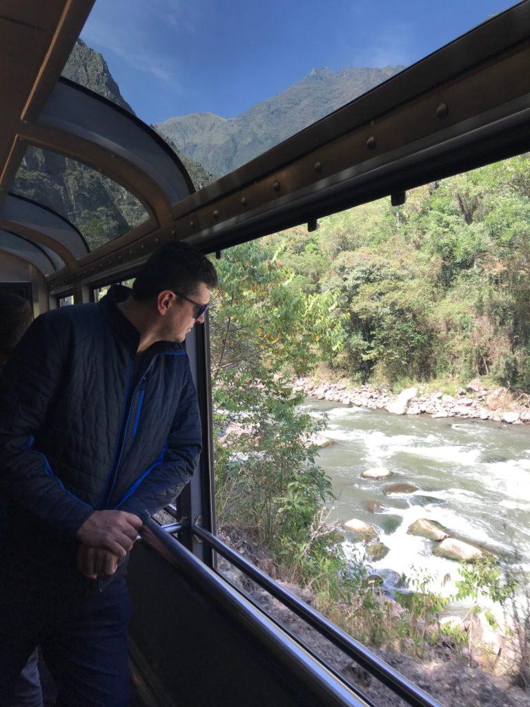 Foto de Flávio Antunes no trem aberto do vagão 360, com vista panorâmica da paisagem entre Cusco e Machu Picchu