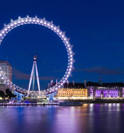 Vista da London Eye, em Londres, com luzes acesas e céu azul escuro ao fundo.