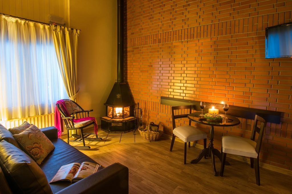 Lua de Mel em Gramado - Sala do quarto do Hotel Recanto da Serra - com lareira, sofá e jantar para dois