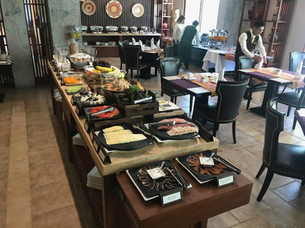 Mesa com opções de frios e diversas frutas para o café da manhã no hotel