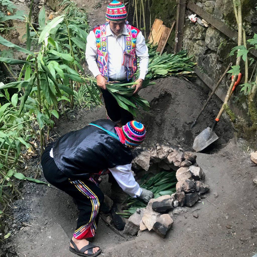 Dois funcionários do Hotel Sumaq montando o forno Pachamanca no solo