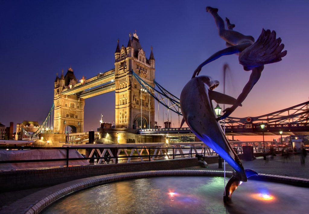 Foto de estátua de golfinho e anjo e Tower Bridge ao fundo, em segundo plano