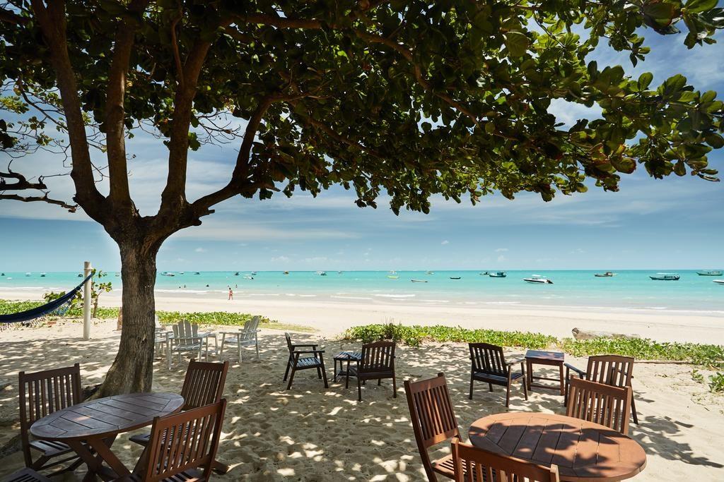 Vista da Pousada Odoiá em Maragogi, direto em praia da cidade, com árvore, cadeiras e mesas na orla.