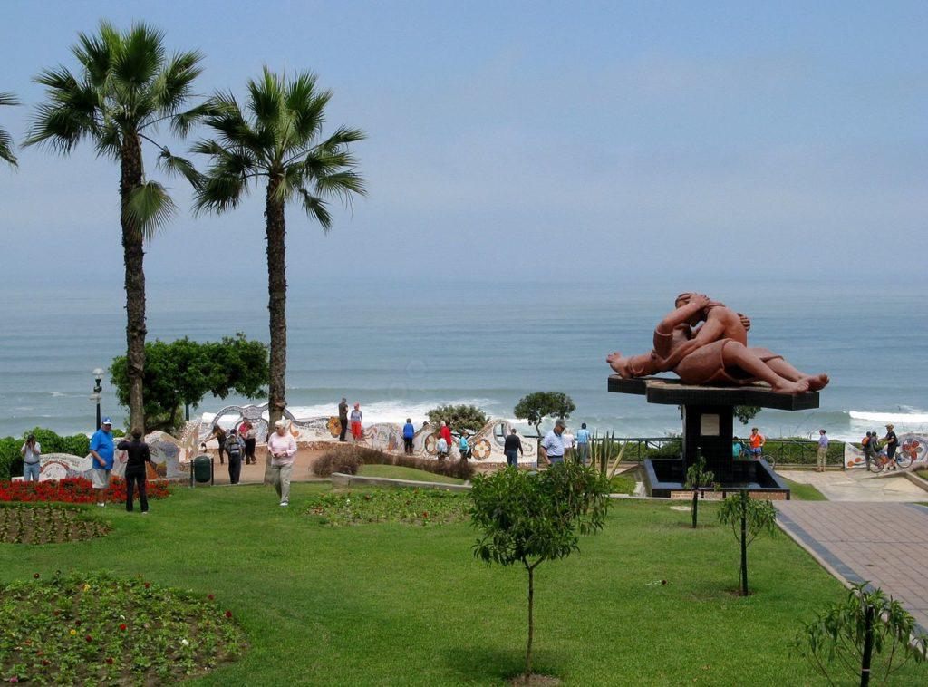 O Parque do Amor, com a estátua El Beso, árvores, pessoas e o oceano Pacífico ao fundo, uma dica de passeio em lua de mel em Lima, no Peru