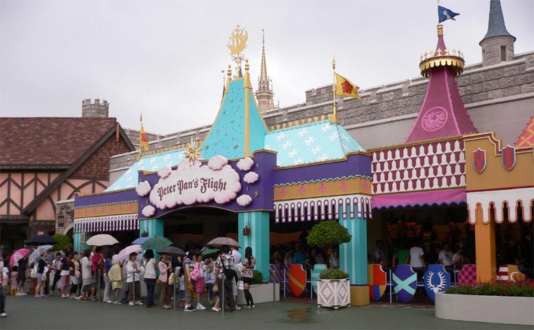 Entrada da Peter Pan's Flight, com fila e pessoas com guarda-chuva.