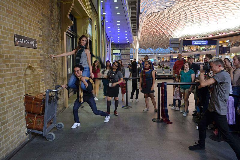 Pessoas posando para foto na estação Kings Cross, em frente ao monumento de Harry Potter