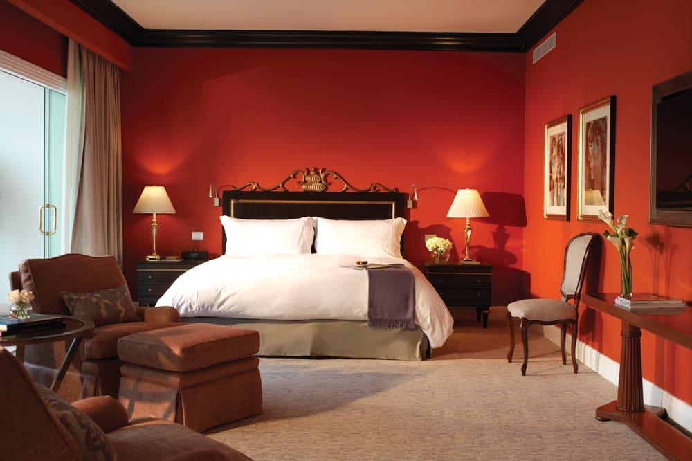 Quarto sofisticado no Belmond Miraflores, com paredes vermelhas e ótima decoração