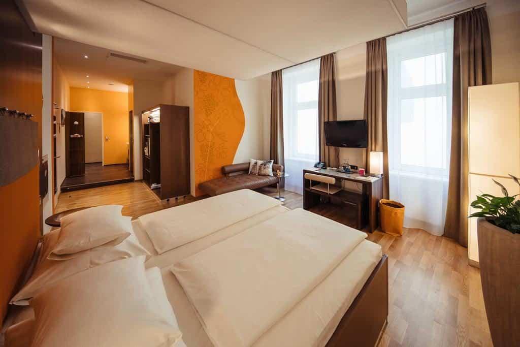 Cama de casal em quarto com TV no Hotel Rathaus