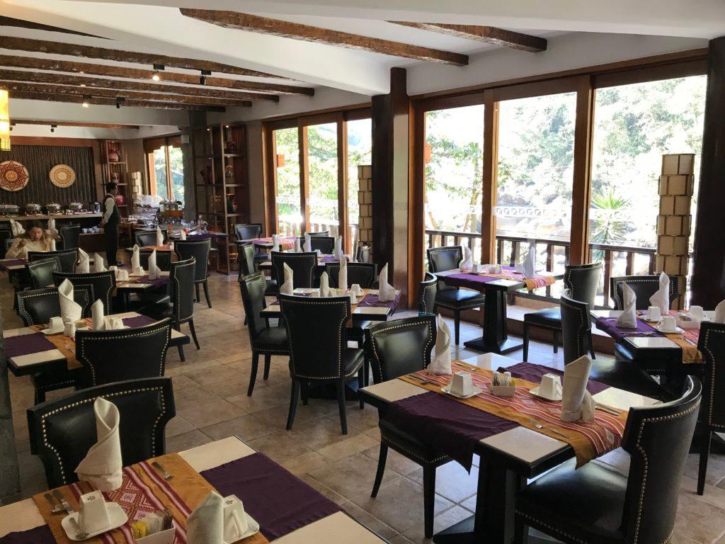 Foto com mesas e cadeiras acolchoadas no restaurante Qunuq, no hotel Sumaq, durante o dia.