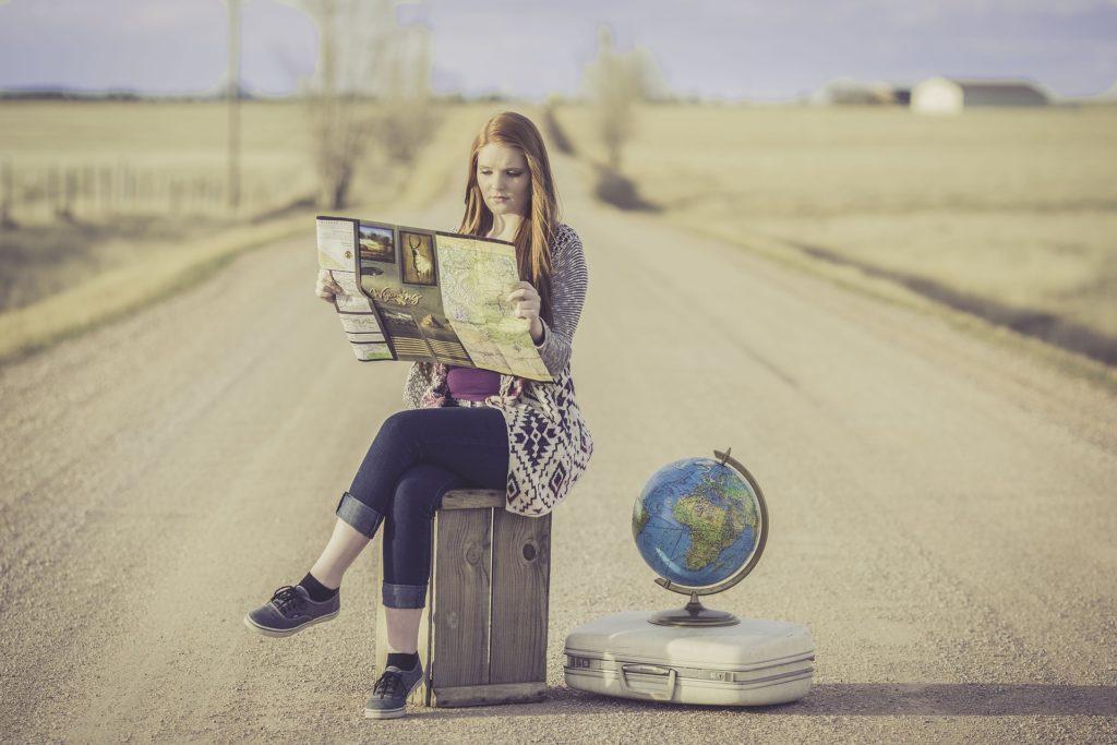 mulher sentada no meio das estrada com um mapa mundo - escolhendo o gta seguro viagem