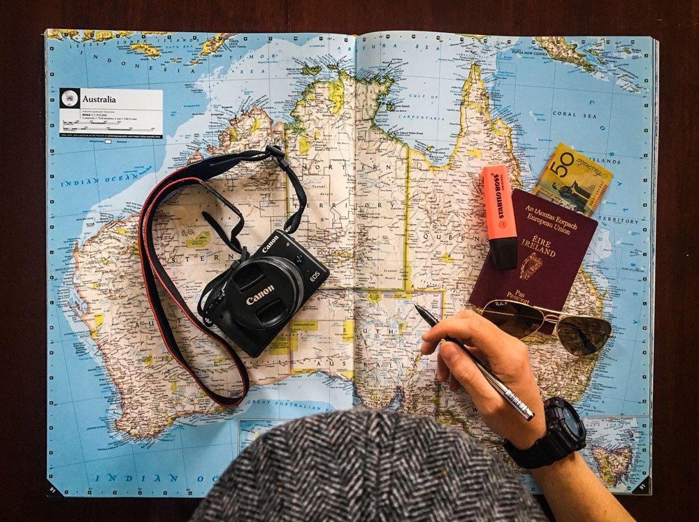 Travel Ace Seguros - homem em frente ao mapa, camera e passaporte - travel ace é bom