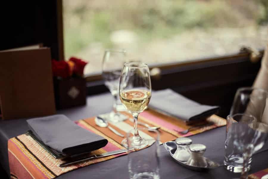 Foto de detalhes da mesa do vagão de primeira classe da Inca Rail. com taça de vinho branco, guardanapos escuros, talheres e conjunto de saleiros.