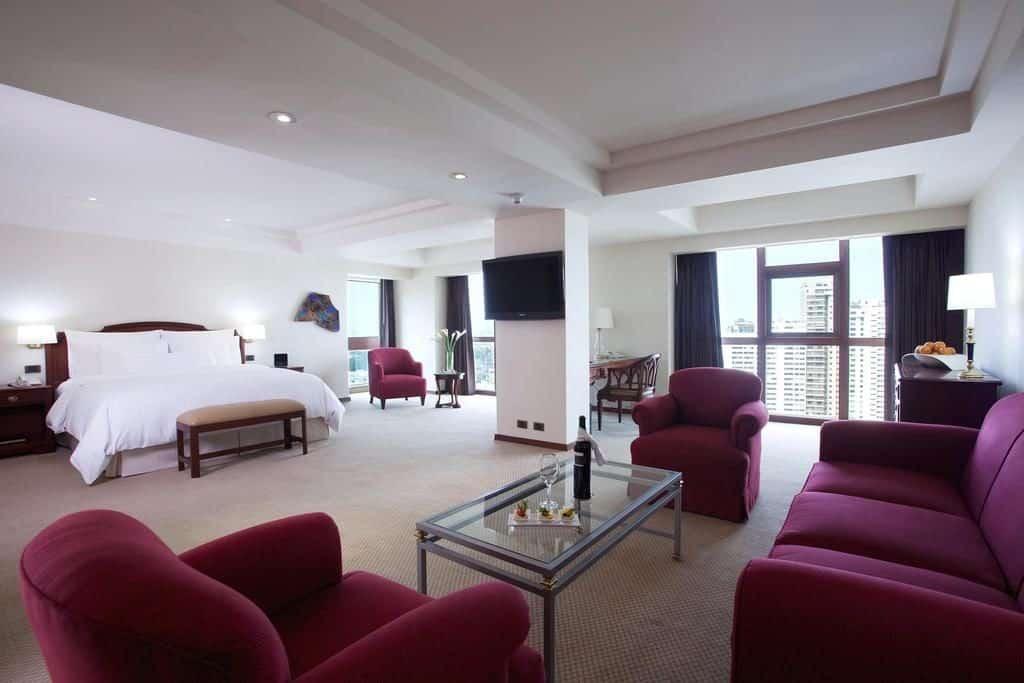Quarto espaçoso com cama king, área de estar, amplas janelas com vista para a cidade e poltronas vermelhas no Swissotel hotel de luxo em Lima