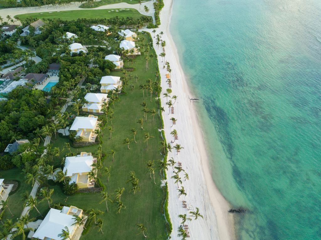 Vista áerea do Tortuga Bay, com quartos estrategicamente posicionados em frente ao mar, e água límpida no oceano.