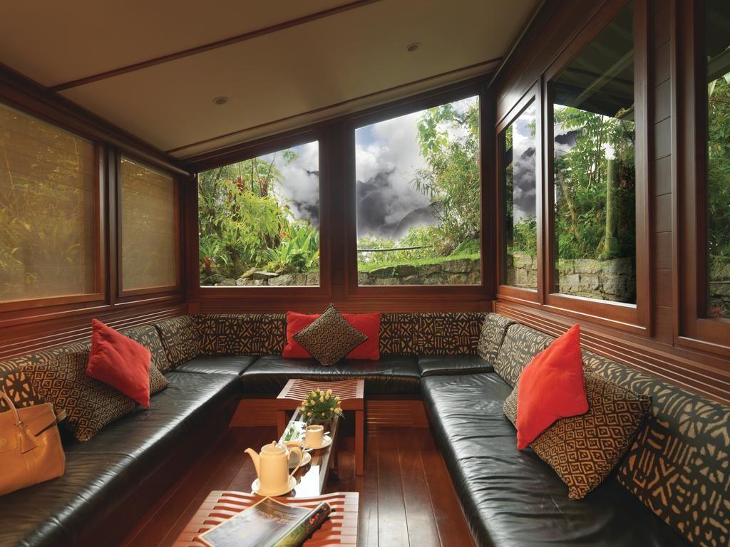 Foto de espaço com sofás, mesinha para chá e almofadas no Belmond Sanctuary Lodge