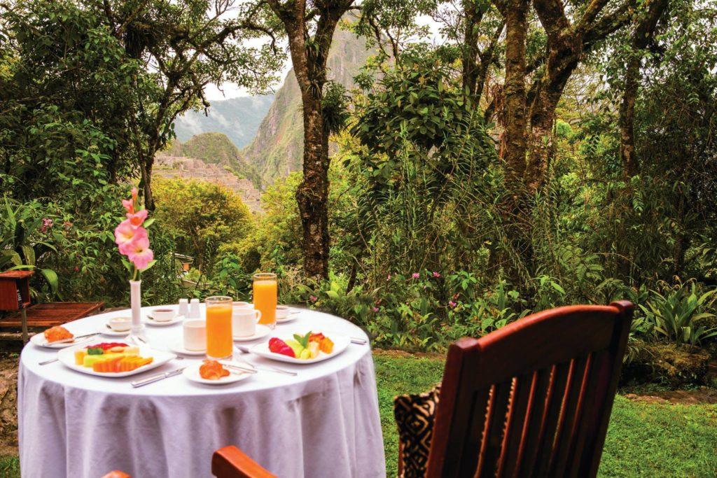 Mesa de café da manhã, com suco e frutas, posta no jardim do Belmond com vista para as montanhas