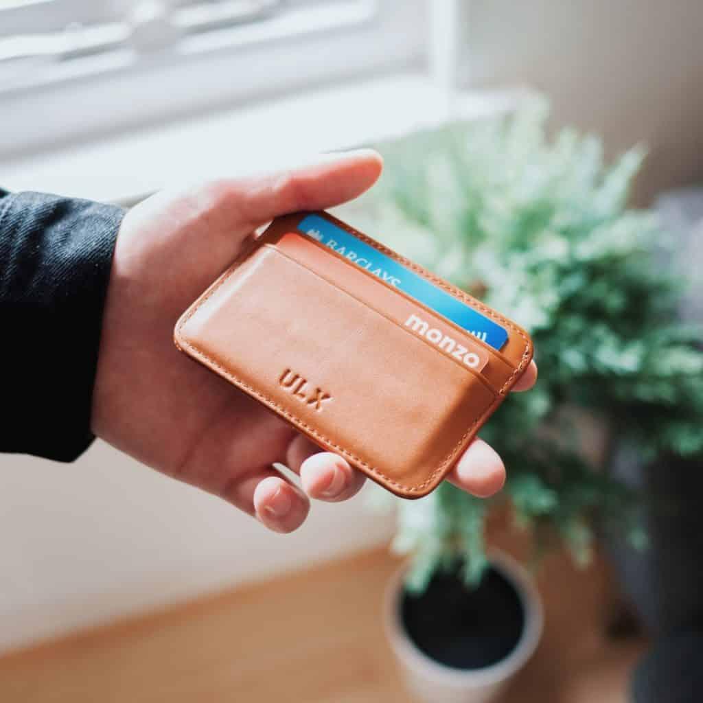 Mão segurando cartões de crédito que, dependendo da bandeira, oferece seguro para aluguel de carro San Francisco