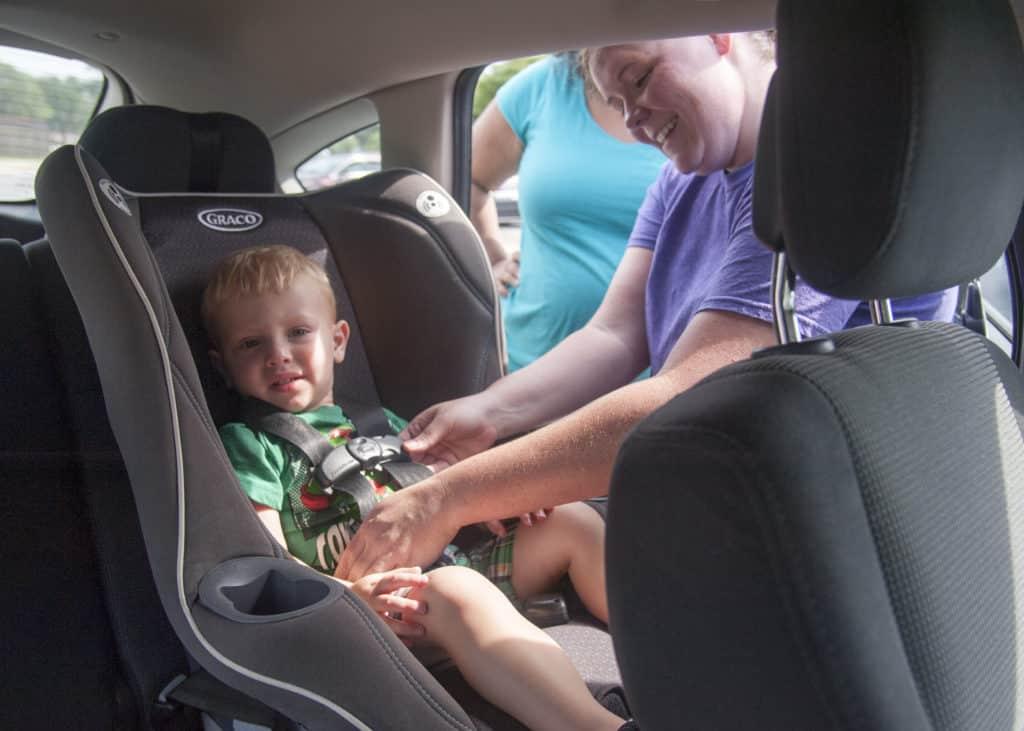 Criança sendo arrumada em cadeirinha de carro, exigência nos Estados Unidos