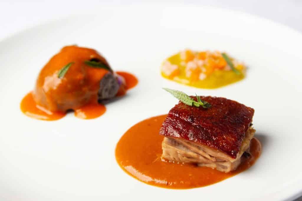 Foto de prato com carne suína e outras porções coloridas desfocadas ao fundo
