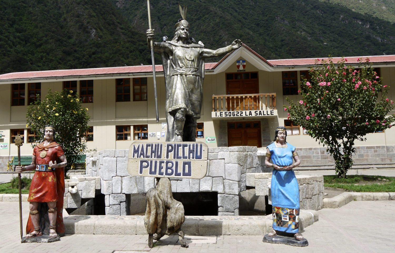 Estátuas no centro de Machu Picchu Pueblo com placa indicativa da cidade.