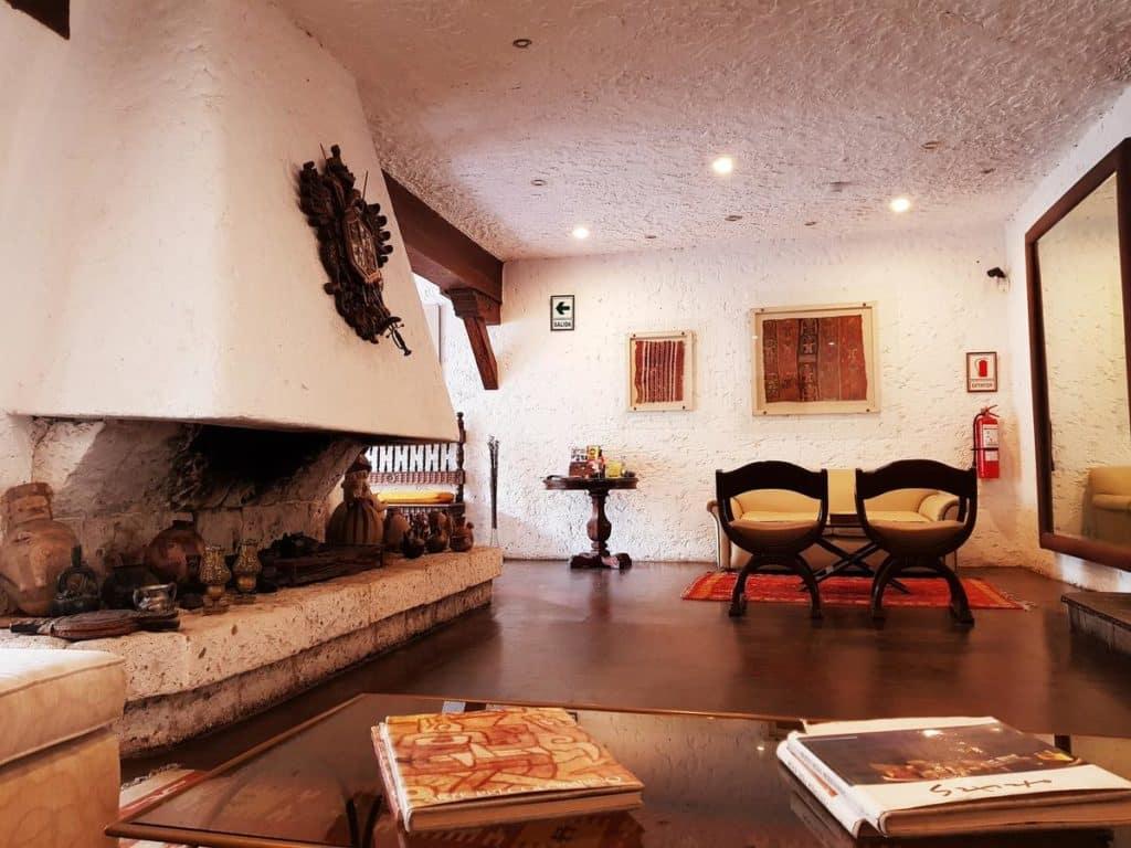 Área comum com lareira e poltronas no Huaca Wasi, hotel de decoração rústica