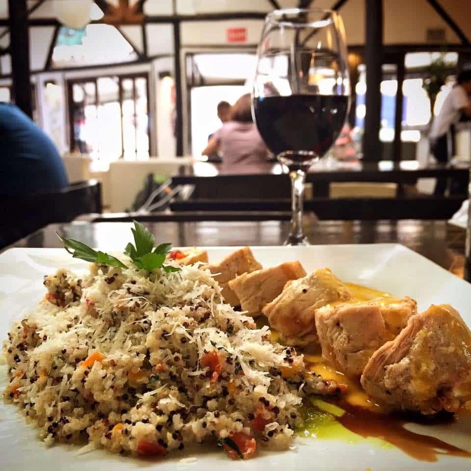 Prato de arroz e frango no Incontri del Pueblo Viejo acompanhado por taça de vinho