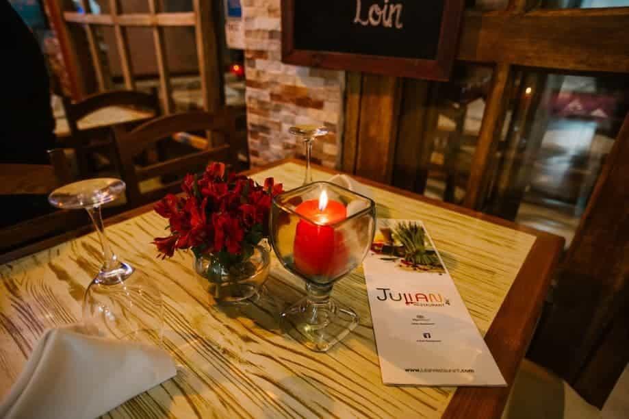 Foto de mesa com flores e vela no Julian Restaurant em Aguas Calientes