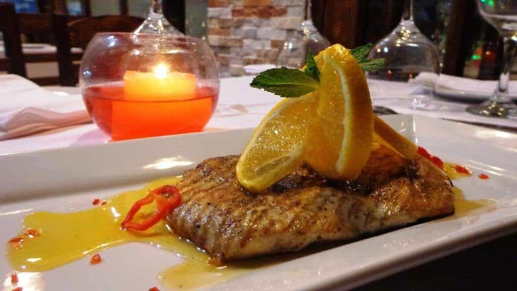 Foto de prato com peixe, molho, pimentas e fruta decorativa, em mexa com vela e taças no restaurante Julian, indicação para lua de mel em Machu Picchu