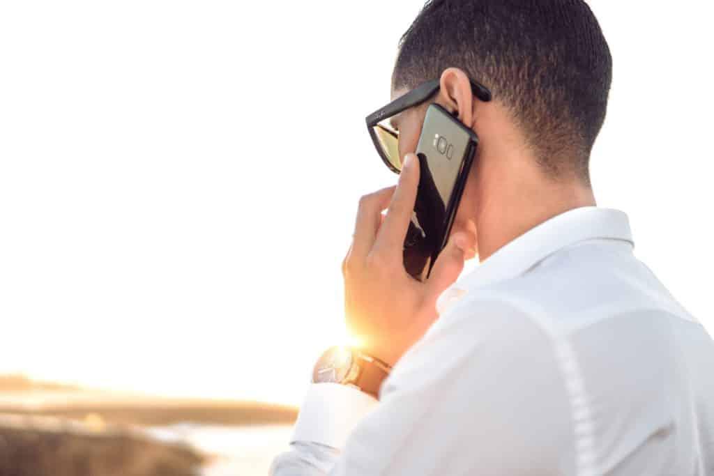 Homem segurando celular durante ligação