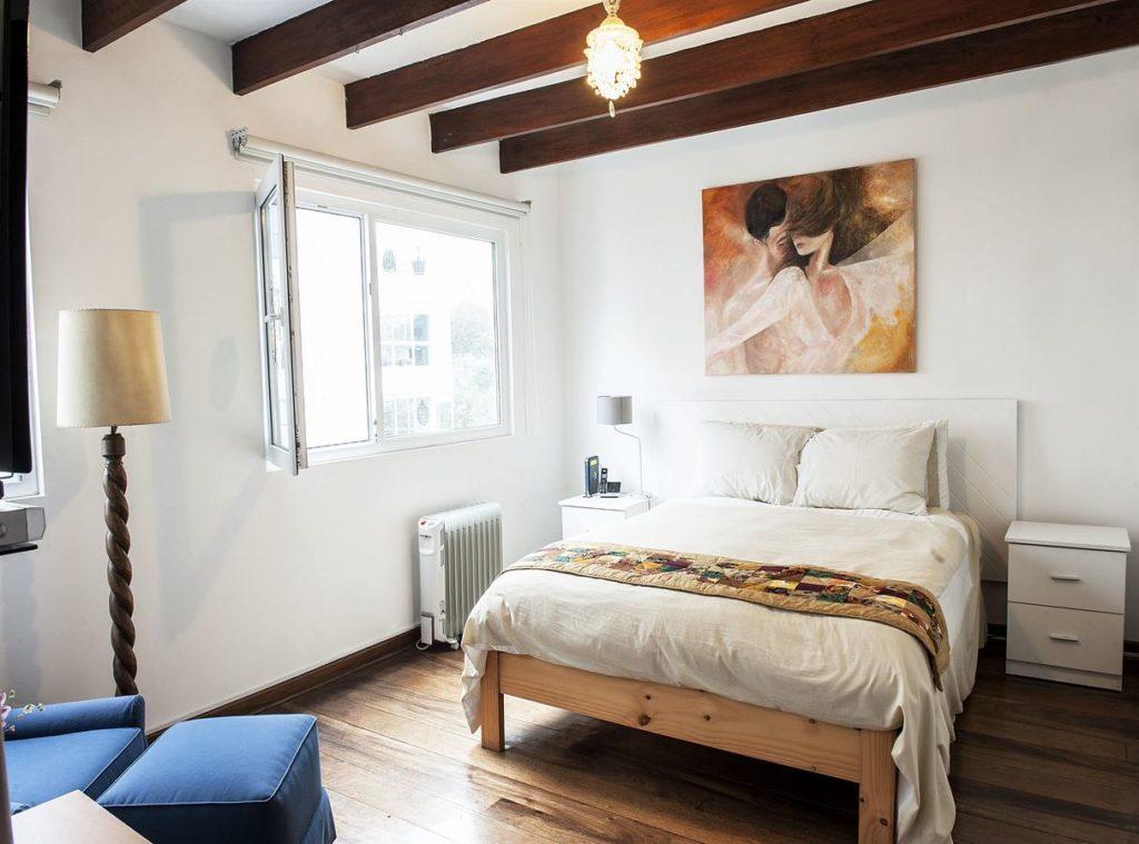 Foto de quarto no Bed & Breakfast Loft en Olivar com cama de casal, janela ampla, quadro e abajur.