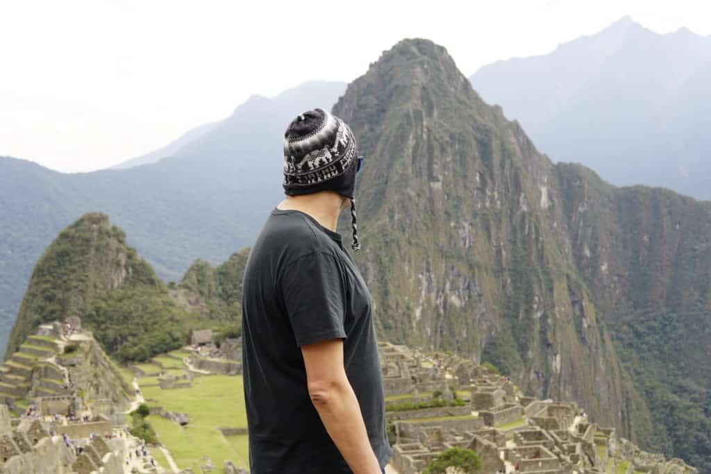Flávio Antunes de costas em foto olhando para a cidadela de Machu Picchu