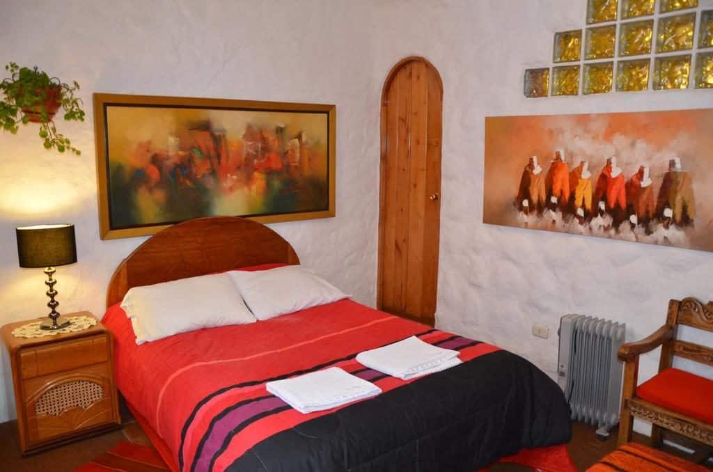 Foto de quarto onde ficar em Machu Picchu no hostal Madre Tierra, com colcha vermelha