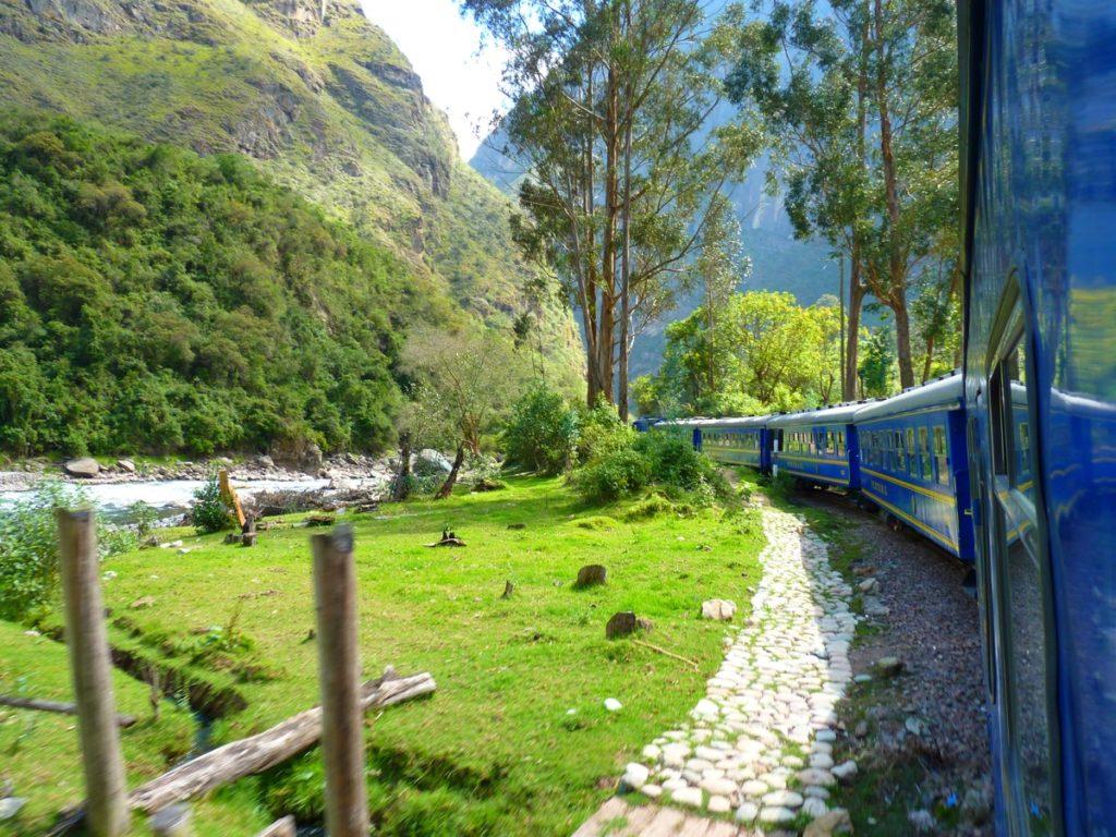 Foto do trem Peru Rail no caminho entre as montanhas para chegar em Machu Picchu