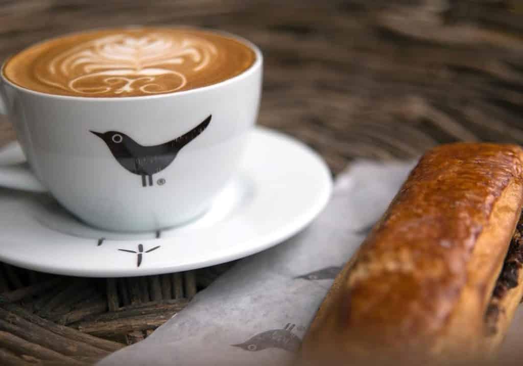 Café com desenho de leite e salgado no Puku Puku Cafe, opção de onde comer em Lima Peru