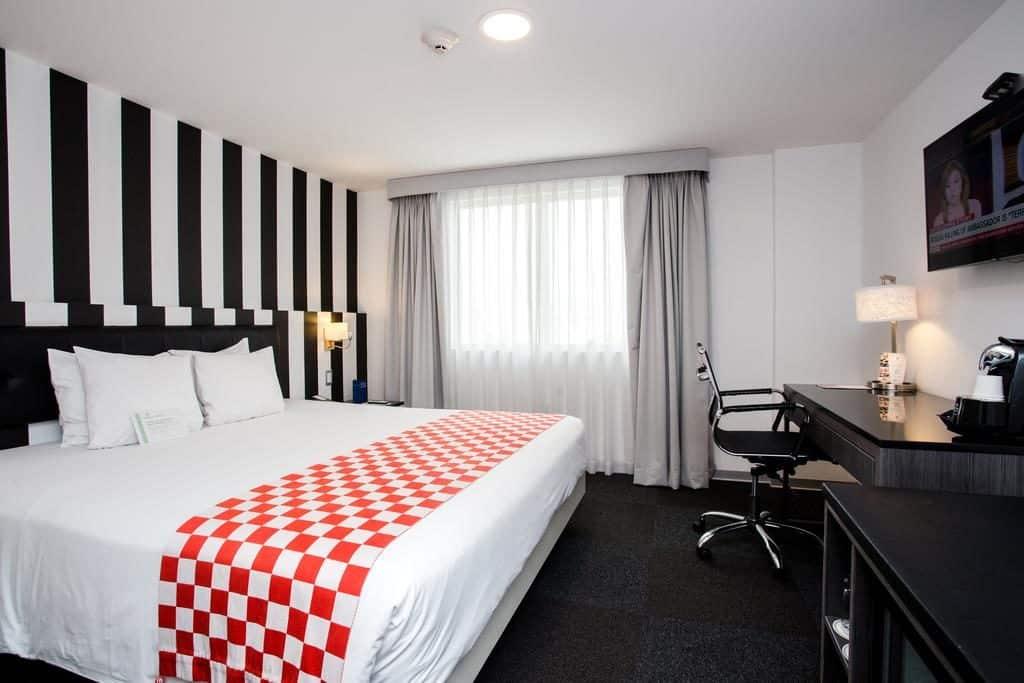 Quarto estiloso no Costa del Sol Wyndham Lima City, com paredes listradas e caminho de cama xadrez.